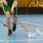 Salibandy turnaus, pelaaja kuljettaa palloa kentällä.